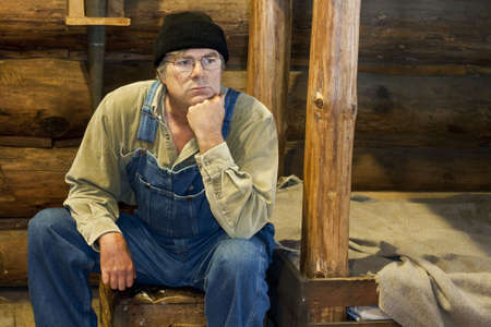 man in bib overalls sitting in his log cabin thinking about life Stock Photo - 8184144