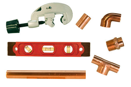 collection of copper pipe fittings with a cutter and level