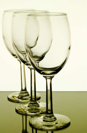 upright row: three wine  glasses in a row standing upright with reflections
