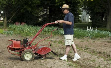 man preparing to till the soil in a garden Stock Photo - 9771306