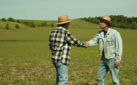 Two farmers shaking hands in a field Standard-Bild - 9861161