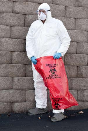 hazardous waste: man in protective suit holding a hazardous waste bag Stock Photo