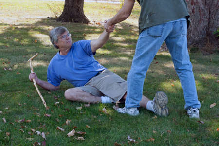man lying on the ground being helped up by a friend Stockfoto