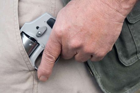concealed: man drawing a concealed weapon from his pants pocket