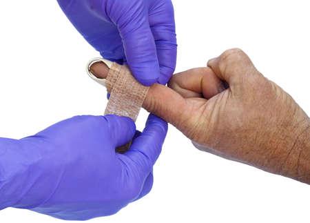 splint: gloved hands applying a splint to an injured finger