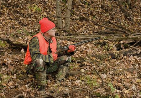 cazador: cazador sentado en el bosque de oto�o de espera para el partido