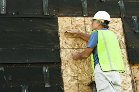 tar paper: man removing tar paper from an old building Stock Photo