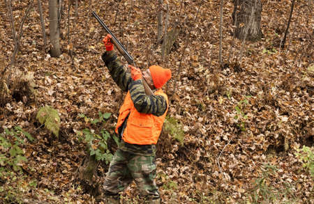 camoflauge: hunter aiming his weapon in the autumn woods Stock Photo