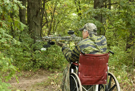 disabled man in wheelchair with a crossbow waiting for action