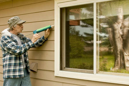 infiltration: workman sealing an exterior window with caulk to reduce air infiltration
