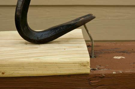 apalancamiento: pata de cabra tirando de un clavo para demostrar el concepto de apalancamiento Foto de archivo