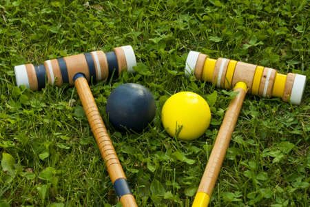 two croquet mallets and balls on a grassy background