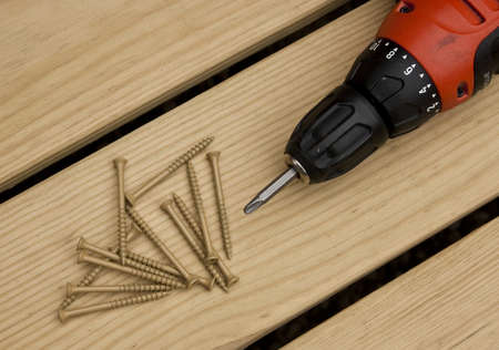 cordless drill and large screws on a wood background