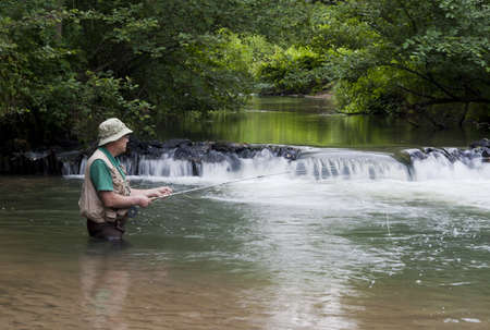 trout fishing: man fishing for trout next to a small waterfall