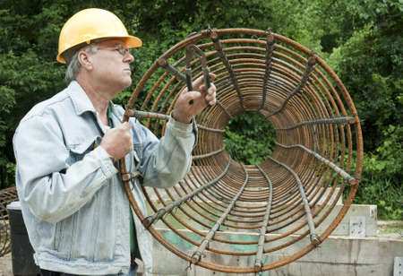 male construction worker assembling rebar forms into a circular shape