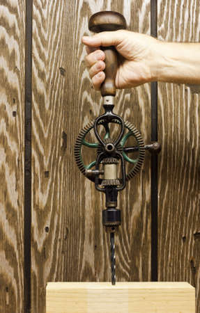 using a retro hand drill to bore a hole in a block of wood