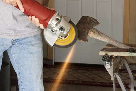 using a grinder to sharpen an axe showing the spark trail Stock Photo