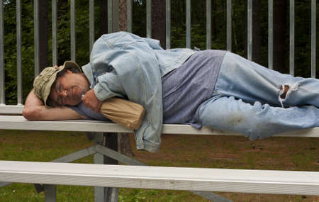 man lying on a bench with a bottle of alcohol in a bag Stock Photo - 15038236
