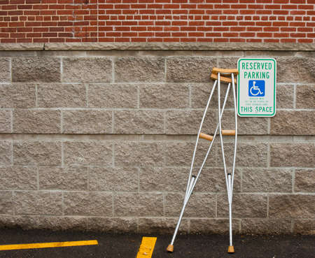 pair of crutches leaning next to a handicapped parking sign photo