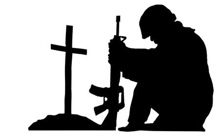 silhouette of a soldier kneeling next to the grave of a friend Stock Photo - 15511082