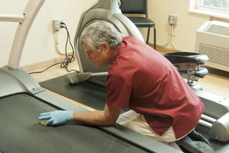 man cleaning the treadmill mat in a workout room