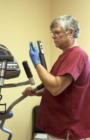 disinfect: maintenance worker using a sponge to disinfect exercise equipment