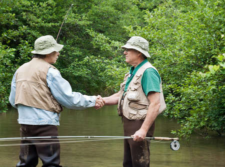 two fisherman shaking hands on a trout stream