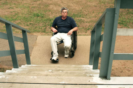man in wheelchair facing a barrier of stairs photo