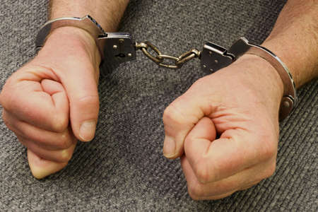 mans hands locked in a pair of handcuffs Stock Photo - 17757857