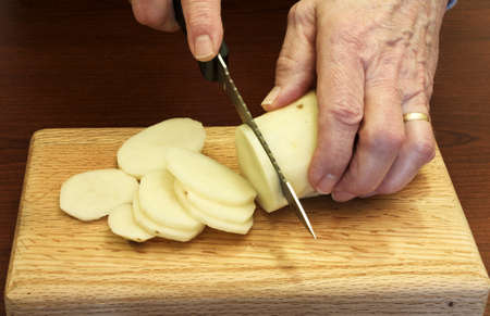 chef slices a potato on a small wooden cutting board Stock Photo