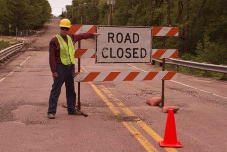 man directing traffic at a road closed sign Stockfoto