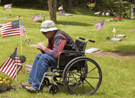 disabled man in a wheelchair visits a fallen brother at the cemetery