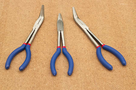 a set of straight and curved long nose pliers