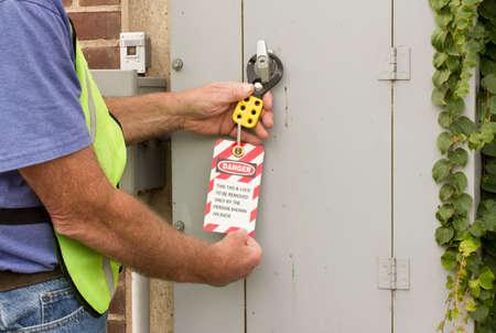 man het bevestigen van een lockout tag om een elektrische bedieningspaneel Stockfoto