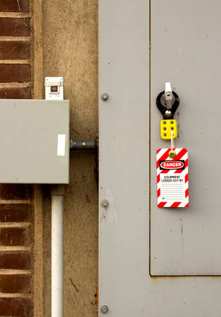 lockout device and tag attached to a large electrical panel Stockfoto