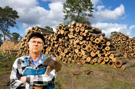 male lumberjack standing in front of a large stack of logs