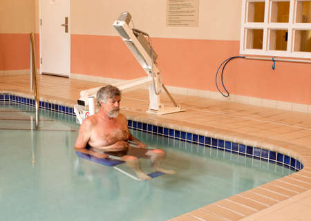 hydraulic lift: disabled man being lowered into a therapy pool with a handicap lift.