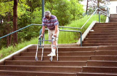 a mature man using a wheeled walker to descend a flight of steep stairs