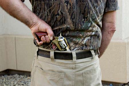 holster: Hombre dibujando una pistola desde el interior de la funda de los pantalones.