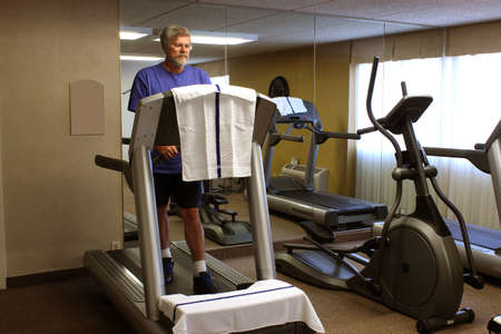 Mature man walking on a treadmill to keep in shape