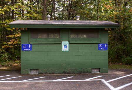 latrine: An outdoor public bathroom located in a wooded park