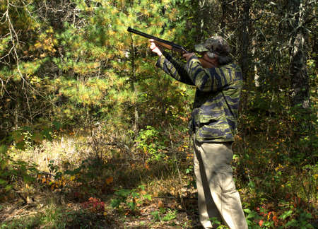 camoflauge: Hunter in the Autumn woods aiming at an unseen target