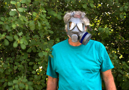 An adult man wearing a gas mask against a wooded background.