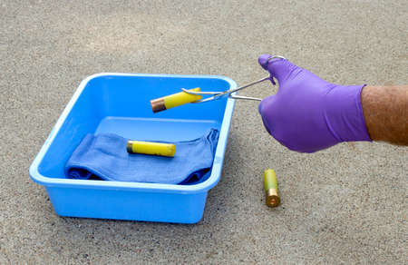 A police investigator picks up shotgun shells from the scene of a crime. 版權商用圖片