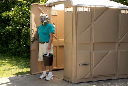 A maintenance worker exits a foul smelling portable bathroom with his cleaning supplies.
