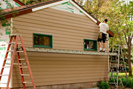 the existing: RIVER FALLS,WISCONSIN-JULY 23,2015: A worker installs Hardie Board siding and flashing to an existing structure.