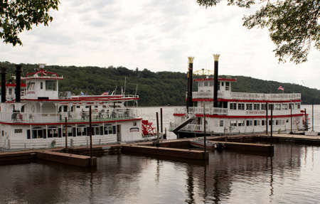 paddle wheel: RIVER FALLS,WISCONSIN-AUGUST 21,2015: Two vintage paddle wheel boats at the docks on a river.