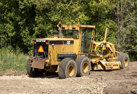 grader: RIVER FALLS,WISCONSIN-SEPTEMBER 13,2015: A Caterpillar brand road grader. Caterpillar is the worlds largest manufacturer of construction and mining equipment.