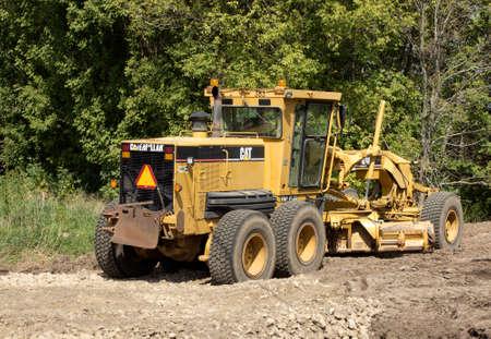 grader: RIVER FALLS,WISCONSIN-SEPTEMBER 13,2015: A Caterpillar brand road grader. Caterpillar is the worlds largest manufacturer of construction and mining equipment.