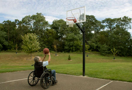 basketball shot: A disabled man in a wheelchair attempts to make a basketball shot. Stock Photo
